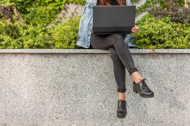 Happy student woman in denim jacket and glasses uses laptop while sitting in the city park
