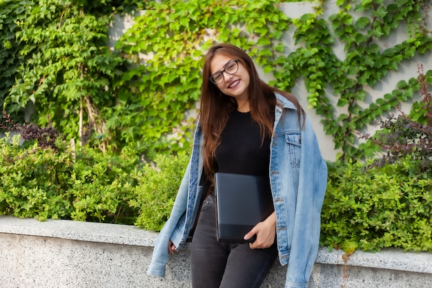 Happy student woman in denim jacket and glasses with laptop in her hands in the city