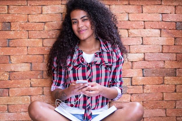 휴대 전화를 사용 하 고 웃 고 벽돌 벽 배경으로 앉아 아프로 헤어 스타일으로 행복 한 학생 여자.