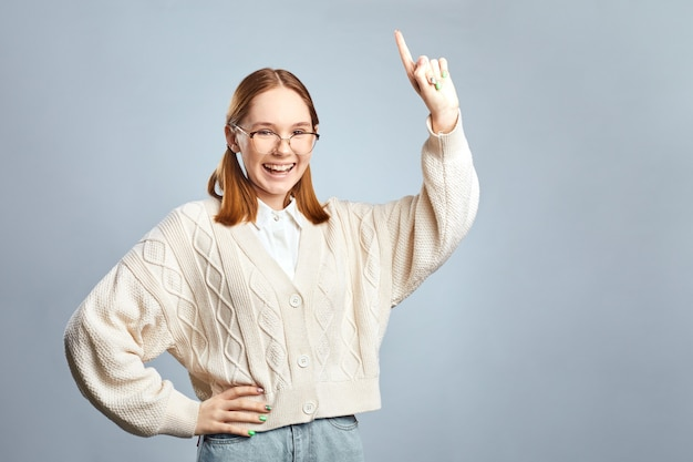 Happy student young woman in eyeglasses and sweater having idea showing finger  over gray wall.