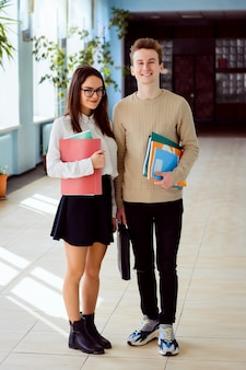 Happy students in corridor of the university in sunny day with books folders and course books ready to study hard and achieve high results