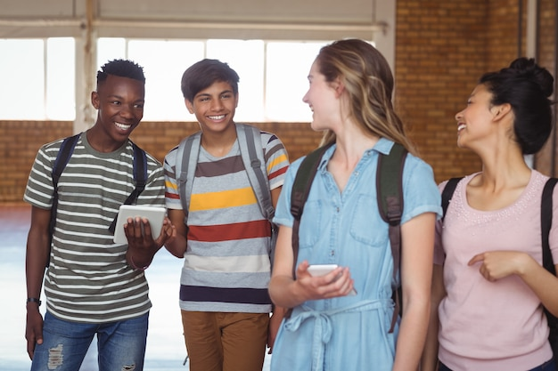キャンパスで携帯電話とデジタルタブレットを使用しながら相互作用する幸せな学生