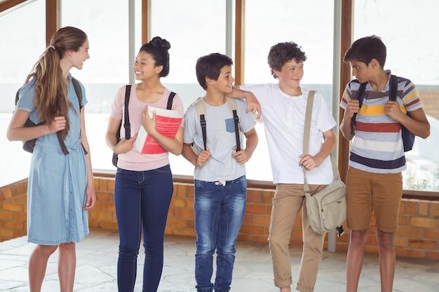 廊下で互いに対話する幸せな学生