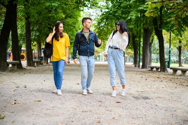 Счастливые студенты гуляют и разговаривают друг с другом на открытом воздухе, в полный рост