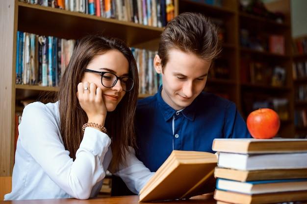 Счастливые студенты вместе читают книгу в библиотеке