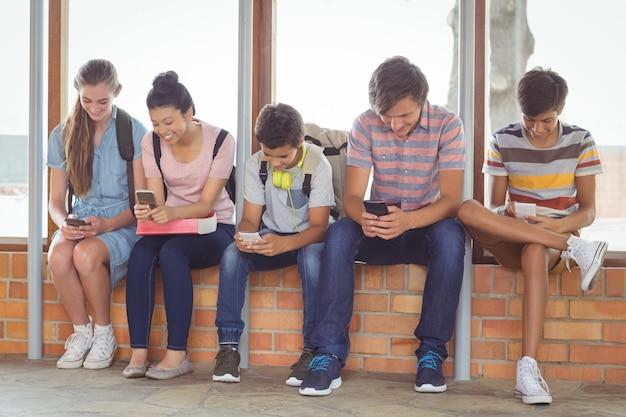 窓枠に座っていると廊下で携帯電話を使用して幸せな学生