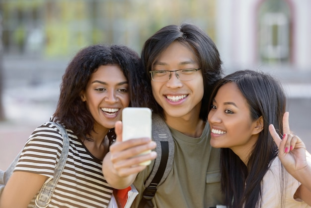 Happy students standing and make selfie outdoors