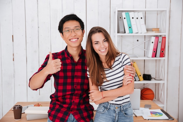 Happy students standing and make thumbs up gesture in classroom