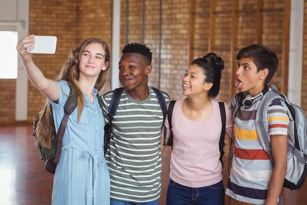 キャンパス内の携帯電話でselfieを取って幸せな学生