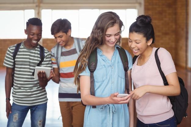 キャンパスで携帯電話とデジタルタブレットを使用して幸せな学生