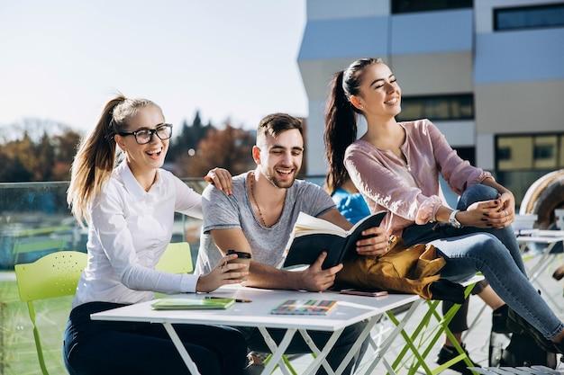 幸せな学生は、新鮮な空気のテーブルで働いて勉強します。