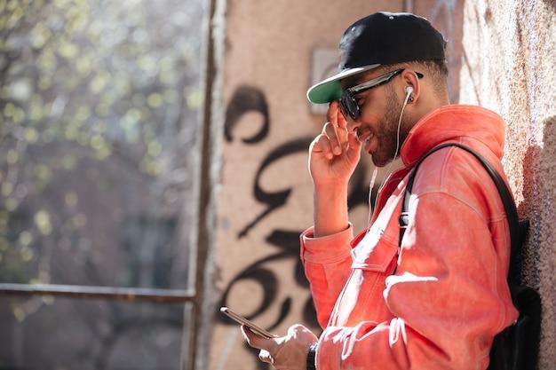 Счастливый стильный афро-американский мужчина в темных очках прослушивания музыки