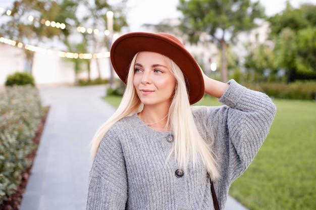 Happy stylish blonde girl wear hat knit woolen jumper outdoors