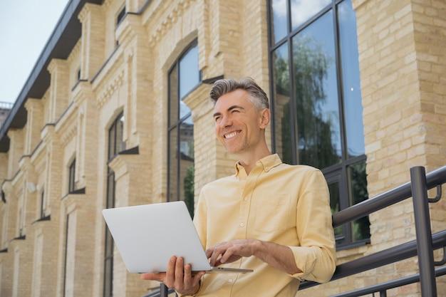 Счастливый стильный бизнесмен с помощью ноутбука, набрав на клавиатуре, смеясь