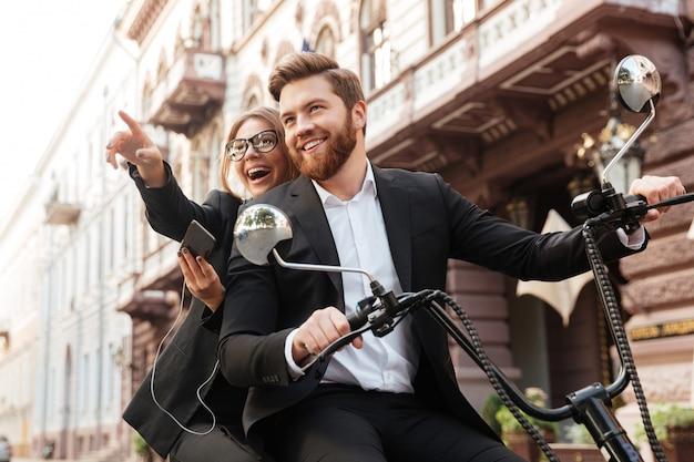 幸せなスタイリッシュなカップルが現代のバイクに乗って屋外