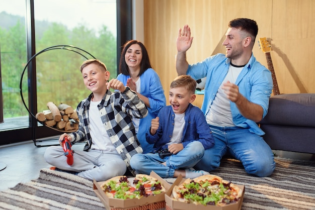 Счастливая стильная семья сидит на полу, играет в видеоигры с геймпадами и ест вкусную пиццу дома
