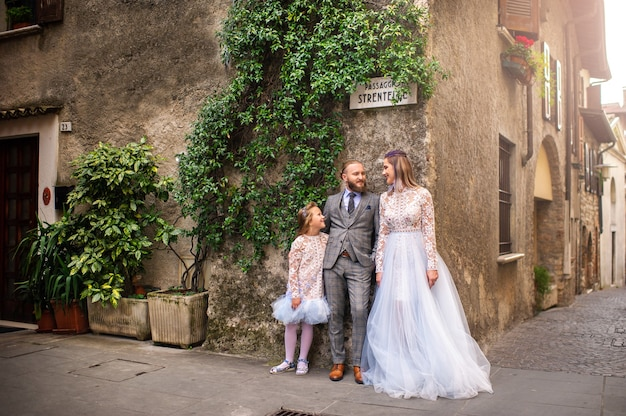 A happy stylish family stands in the old town of sirmione in italy