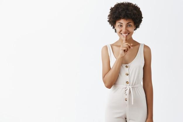 白い壁にポーズをとって幸せなスタイリッシュな女の子