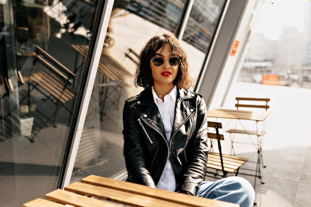 Happy stylish girl with short hair wearing glasses and leather jacket with red lips resting on summer terrace in sunlight
