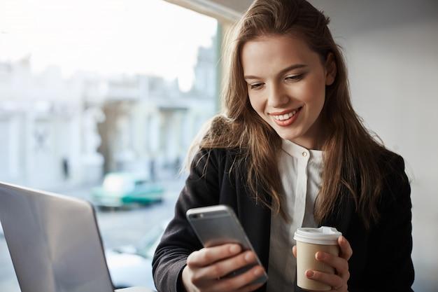 행복 세련된 잘 생긴 여자 학생 커피 숍에 앉아 음료를 마시고 스마트 폰을 통해 메시징, 노트북으로 프로젝트 작업