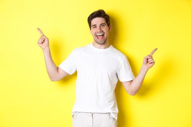 黄色の背景の上に立って、左右のプロモーションで指を横向きにした2つのバリエーションを示す幸せなスタイリッシュな男。