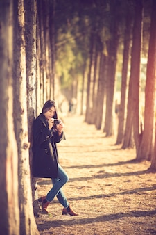 Happy and stylish hipster woman taking photo with photo camera on background