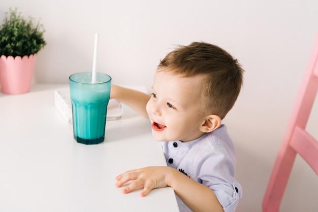 ミルクセーキと幸せなスタイリッシュな小さな男の子 Premium写真