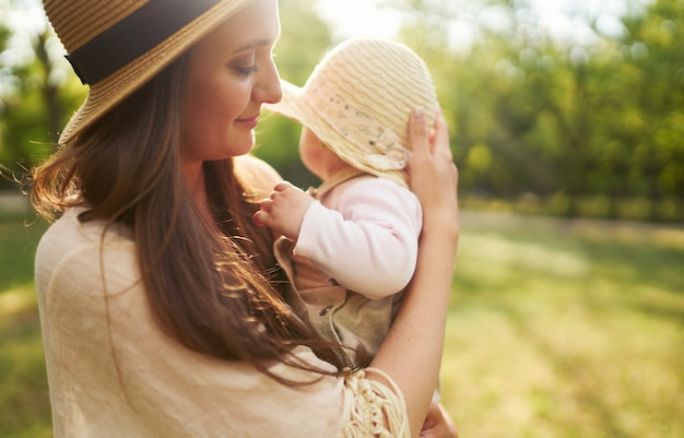Happy stylish and loving family. mother playing with her baby outdoor. lovely baby smiles and enjoys. mother's day concept.