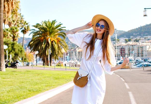Счастливая стильная великолепная женщина, развлекающаяся на красивой пристани для яхт во франции