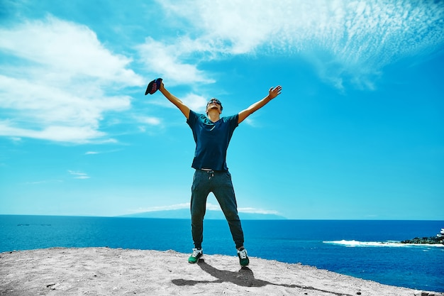Happy stylish man in casual clothes standing on the cliff of mountain