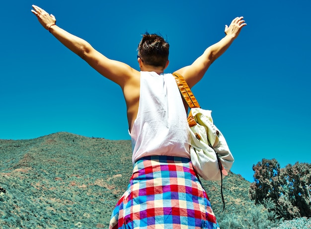Happy stylish man in casual hipster clothes jumping in front of mountain with raised hands to the sun and celebrating success