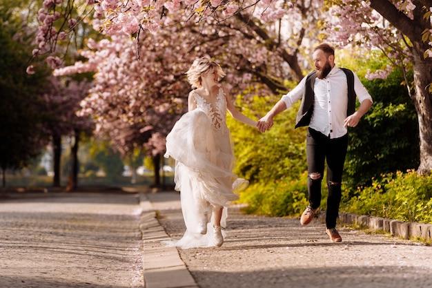 ひげを持つ幸せなスタイリッシュな男とロングドレスの女性は、春に咲く桜公園で楽しんでいます。公園で新婚のヒップホップカップル。新婚。公園を走り、手をつないでください。