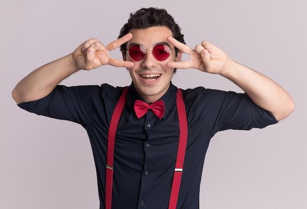 眼鏡とサスペンダーを身に着けている蝶ネクタイと幸せなスタイリッシュな男は、白い壁の上に立っている目の近くにvサインを示して笑顔を正面に見ています