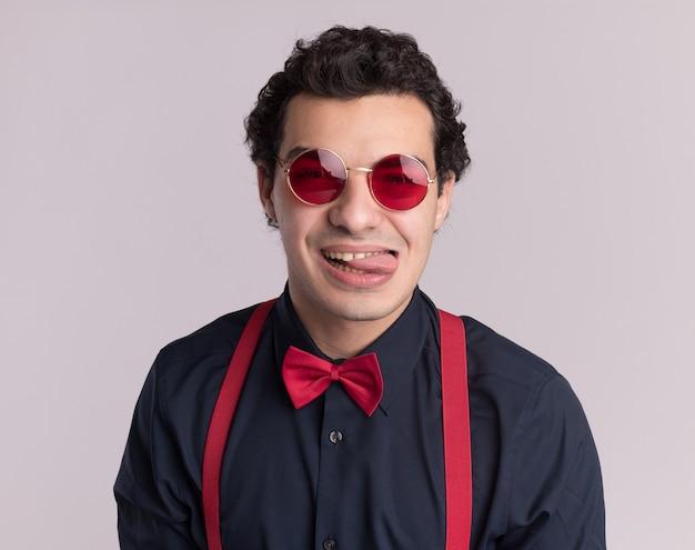 흰 벽 위에 서있는 혀를 튀어 나와 앞을보고 안경과 멜빵을 착용하는 나비 넥타이와 함께 행복 세련된 남자