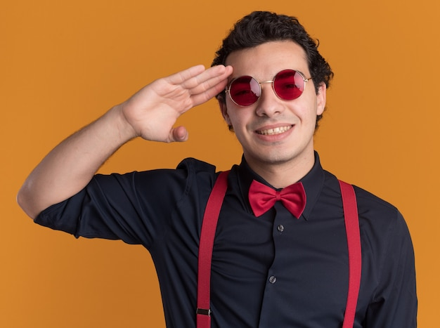 Happy stylish man with bow tie wearing glasses and suspenders looking at front with smile on face saluting standing over orange wall
