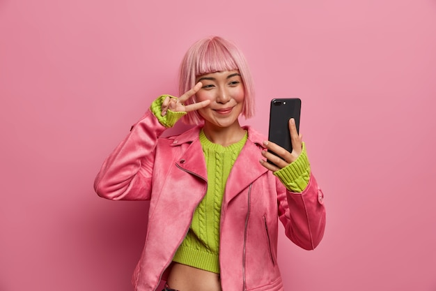 Happy stylish millennial girl shows two fingers over eye, peace sign, takes selfie, enjoys her new hairstyle, dyed hair in pink
