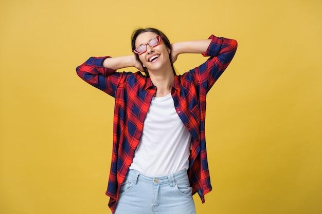 黄色の背景に分離されたカメラを見て笑っているモダンな形のサングラスと幸せなスタイリッシュな現代女性。幸福の概念
