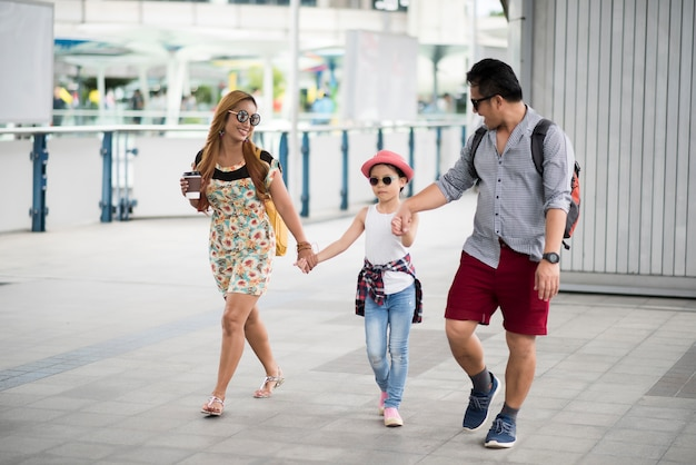 Happy stylish parents holding hands with daughter walking on street in the city