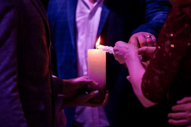 Счастливая стильная свадебная пара держит свечи с огнем и зажигает их свечой от родителей, семейная традиция огня на стойке регистрации. жених и невеста в священном браке.