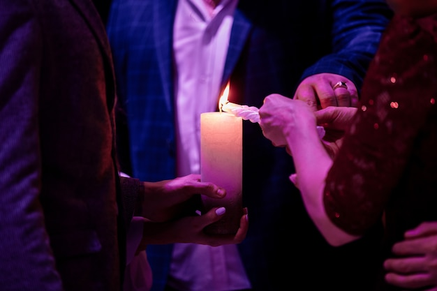 Happy stylish wedding couple holding candles with fire and light them up with candle from parents, family fire tradition at reception. bride and groom at holy matrimony.