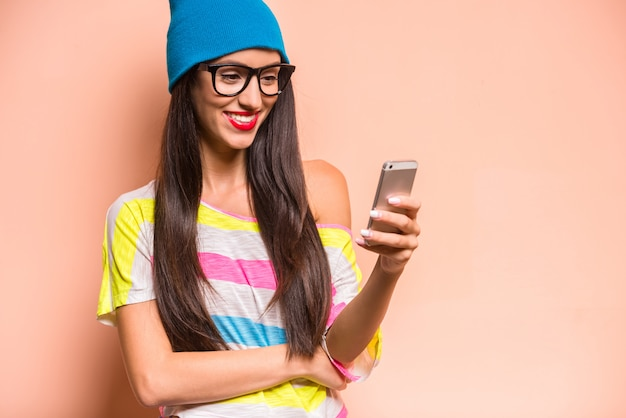 Happy stylish woman in colored clothes using smartphone.