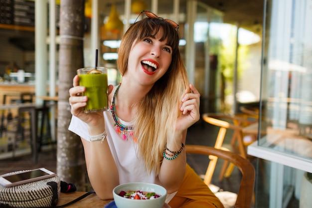 Donna alla moda felice che mangia alimento sano che si siede nel bello interno con i fiori verdi