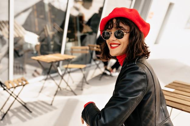 Felice donna elegante in abito francese con labbra rosse e berretto rosso seduto in terrazza all'aperto