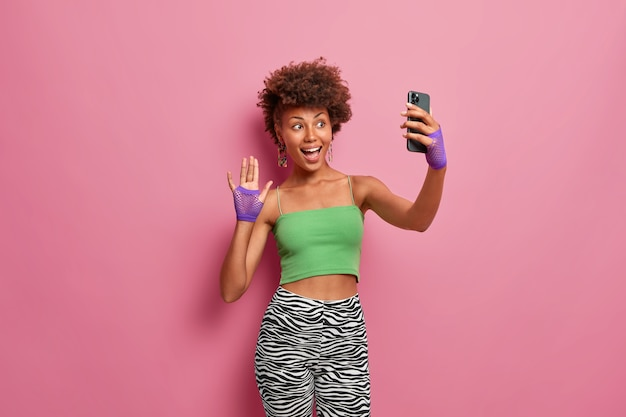 Happy stylish woman in green cropped top and leggings, sport gloves, waves hand at camera of smartphone, greets followers on her blog