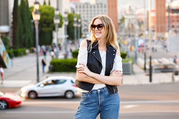 Happy stylish woman posing on european street