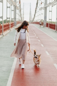 Happy stylish woman walking with her corgi