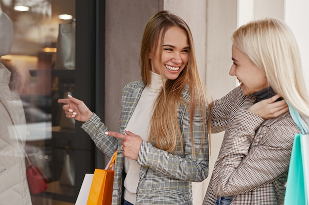 Happy stylish women with paper bags pointing at coat in shop window and looking at each other while standing on city street