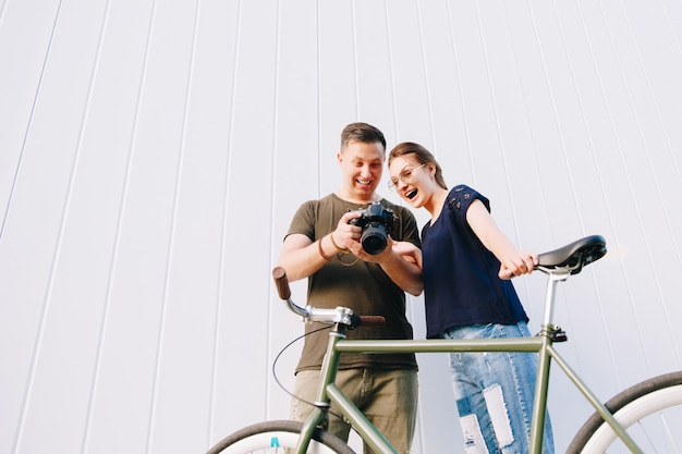 Happy stylish young couple, man and woman standing with bike, looks exciting while watching photos in the camera after photo shooting, outdoors.
