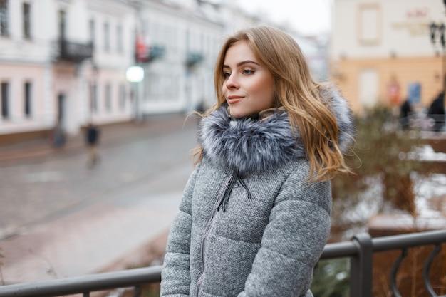 아름 다운 미소와 니트 따뜻한 장갑에 모피와 세련 된 겨울 코트에 회색 니트 모자에 행복 세련 된 젊은 여자는 겨울 날에 도시 주변을 산책. 귀여운 소녀