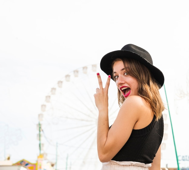 Happy stylish young woman showing peace sign at amusement park